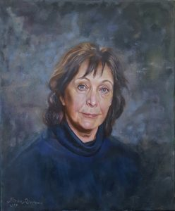 An oil painting on panel of a woman wearing a blue poloneck, and where sand is mingled in the oil paint of the background.