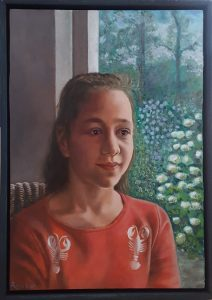An oil painting on wood of a girl wearing a red sweater upon which scorpios are depicted.