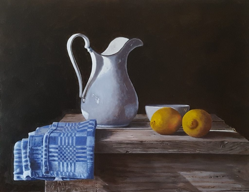 A still life with an old white enamel water or milk jug, a blue dishcloth, a porcelain bowl and two lemons.