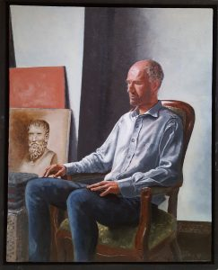 An oil painting on wood of a philosopher sitting in a chair, seemingly contemplating the ancient Greek philosopher Herakleitos.